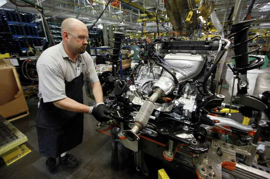 Paul Sancya : Associated Press MAKING FORDS: A worker moves an engine on the assembly line for a Ford Focus this month at a plant in Wayne, Mich. Factory output is rising in the United States. Photo: Paul Sancya / Copyright: Associated Press