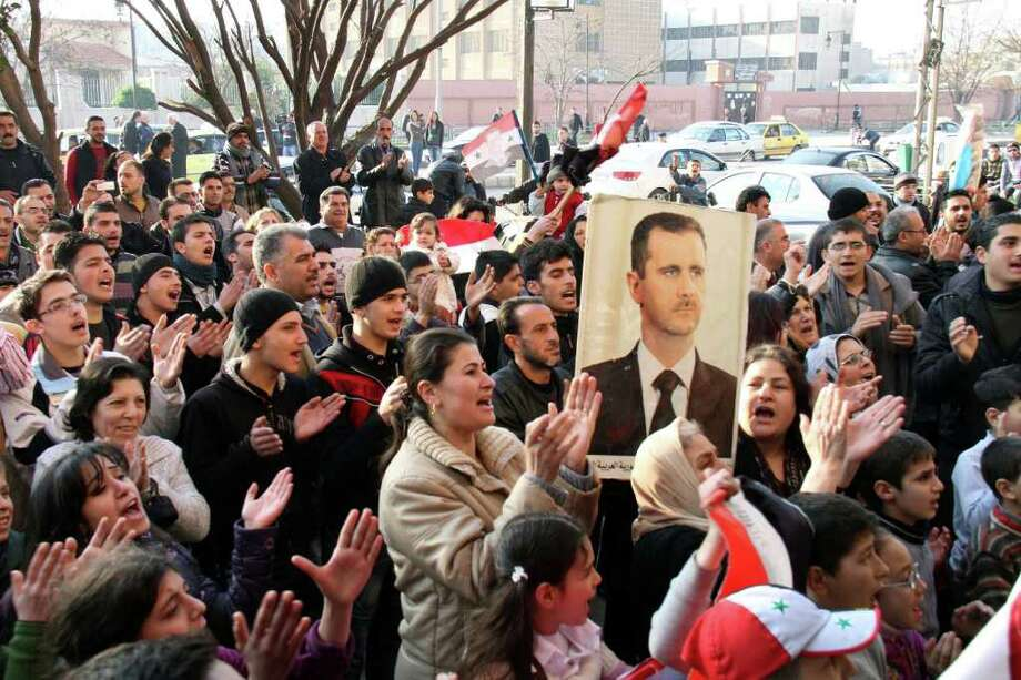 Pro-Syrian regime protesters chant slogans while one holds a picture of President Bashar Assad in the flashpoint city of Homs in central Syria, Thursday, Dec. 29, 2011. Photo: Bassem Tellawi, AP / AP
