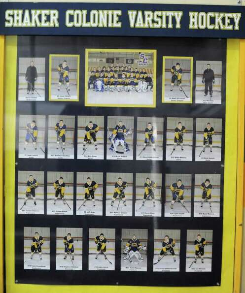 A glass enclosed display of photos of Colonie/Shaker hockey team at the Albany County Hockey Facilit
