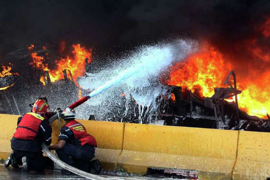 AFP/GETTY IMAGES ABLAZE: Firemen battle the tanker fire on a Caracas highway on Thursday. At least 13 people were killed and 16 wounded when a truck carrying gasoline overturned and exploded. Photo: HO / AFP