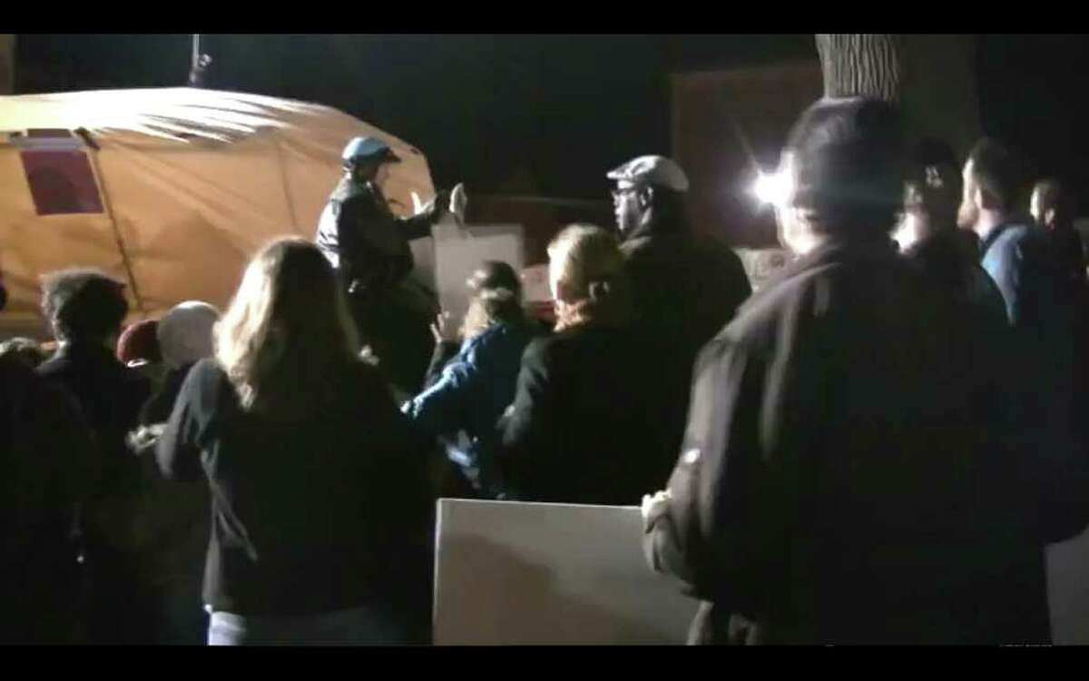 Video frame grab showing the moment when a horse mounted police officer used pepper spray on Occupy Albany members during a clash with police. (Marie Anne Sheehan)