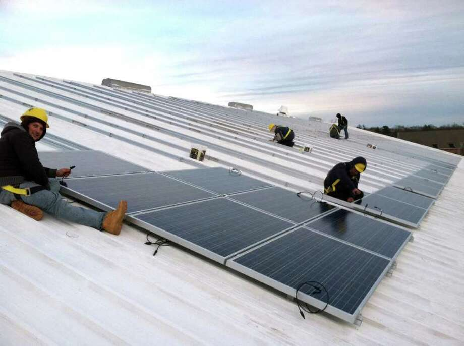 Workers install solar panels on the roof of the Greenwich Racquet Club on River Road in Cos Cob. The project, designed and overseen by Greenwich-based Sound Solar Systems, should be completed by the end of February. Photo: Contributed Photo