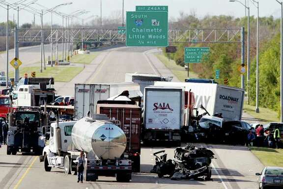 Several vehicles lie mangled in the westbound lane of I-10 between I-510 and Michoud Boulevard in eastern New Orleans, Thursday, Dec. 29, 2011. Police said two men died and 59 people were hurt in a predawn pileup of about 40 vehicles that closed heavily trafficked Interstate 10 in eastern New Orleans through rush hour and beyond. (AP Photo/The Times-Picayune, Eliot Kamenitz)