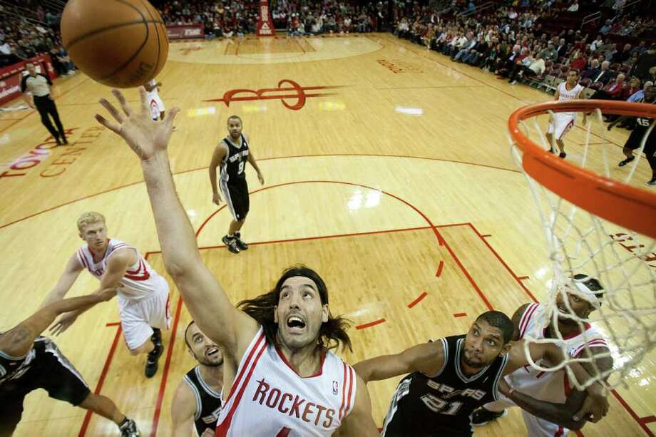 Houston Rockets power forward Luis Scola (4) reaches for a rebound against San Antonio Spurs center Tim Duncan (21) and shooting guard Manu Ginobili (20) during the first half of an NBA basketball game at Toyota Center on Thursday, Dec. 29, 2011, in Houston. Photo: Smiley N. Pool, Houston Chronicle / © 2011  Houston Chronicle