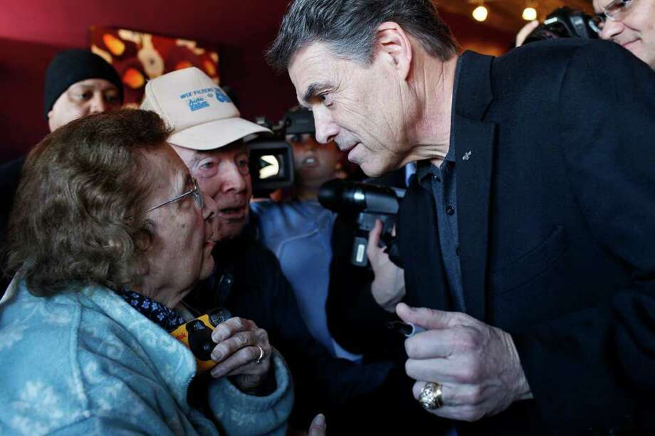 LISA KRANTZ : SAN ANTONIO EXPRESS-NEWS MEET AND GREET: Gov. Rick Perry was warmly greeted by Wanda Zuehlke and Lane Morgan after he spoke at a meet and greet at the Coffee Corner in Washington, Iowa, on Thursday. Greg Jansen of Tallahassee, Fla., said he was very impressed with Perry's speech but was still making up his mind about whom to support. Photo: LISA KRANTZ / SAN ANTONIO EXPRESS-NEWS
