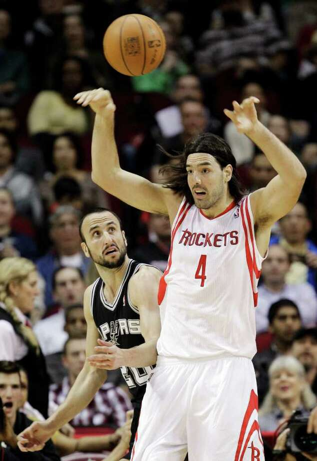 Houston Rockets' Luis Scola (4), of Argentina, passes the ball as San Antonio Spurs' Manu Ginobili (20), of Argentina, defends during the first quarter of an NBA basketball game, Thursday, Dec. 29, 2011, in Houston. (AP Photo/David J. Phillip) Photo: Associated Press
