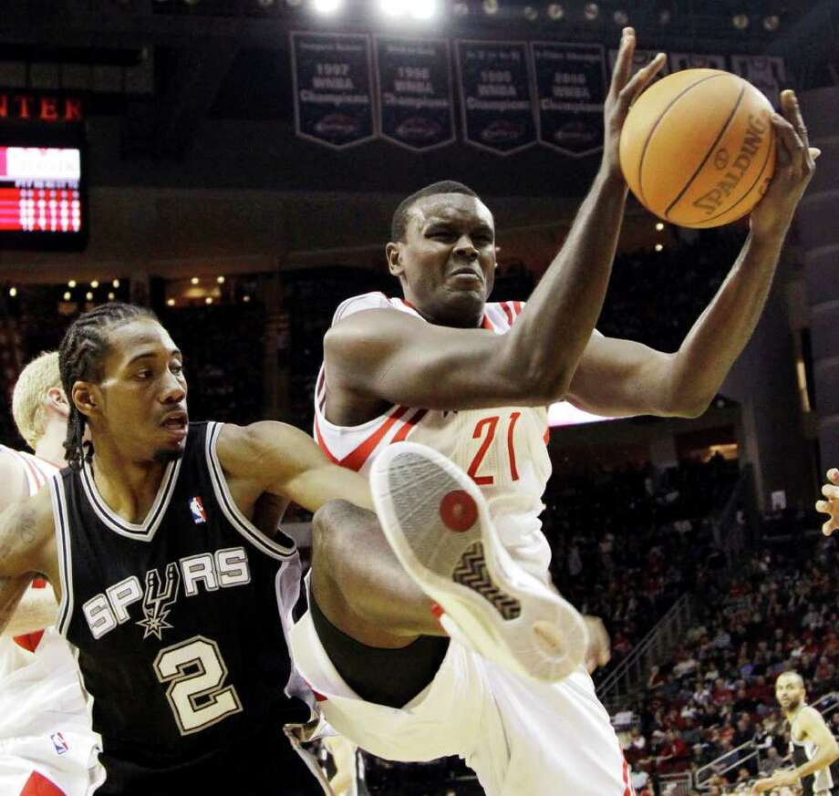 Houston Rockets' Samuel Dalembert (21) pulls down a rebound in front of San Antonio Spurs' Kawhi Leonard (2) during the first quarter of an NBA basketball game, Thursday, Dec. 29, 2011, in Houston. (AP Photo/David J. Phillip) Photo: Associated Press