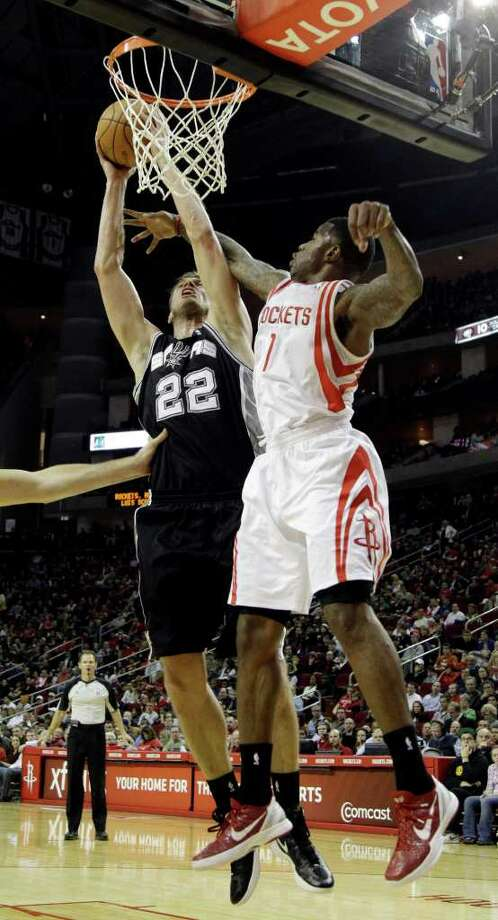 San Antonio Spurs' Tiago Splitter (22) is fouled by Houston Rockets' Terrence Williams (1) during the second quarter of an NBA basketball game, Thursday, Dec. 29, 2011, in Houston. (AP Photo/David J. Phillip) Photo: Associated Press