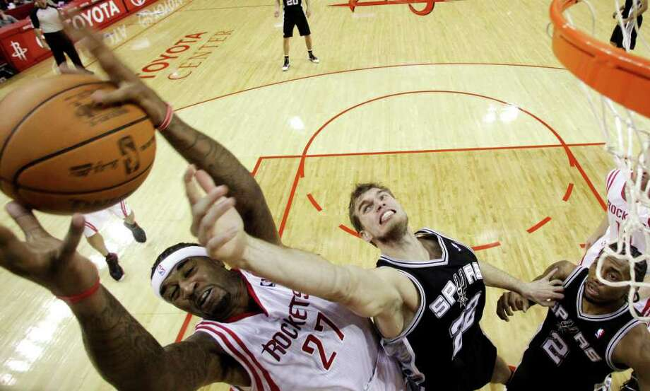 Houston Rockets' Jordan Hill (27) and San Antonio Spurs' Tiago Splitter (22) reach for a rebound during the third quarter of an NBA basketball game, Thursday, Dec. 29, 2011, in Houston. The Rockets beat the Spurs 105-85. (AP Photo/David J. Phillip) Photo: Associated Press