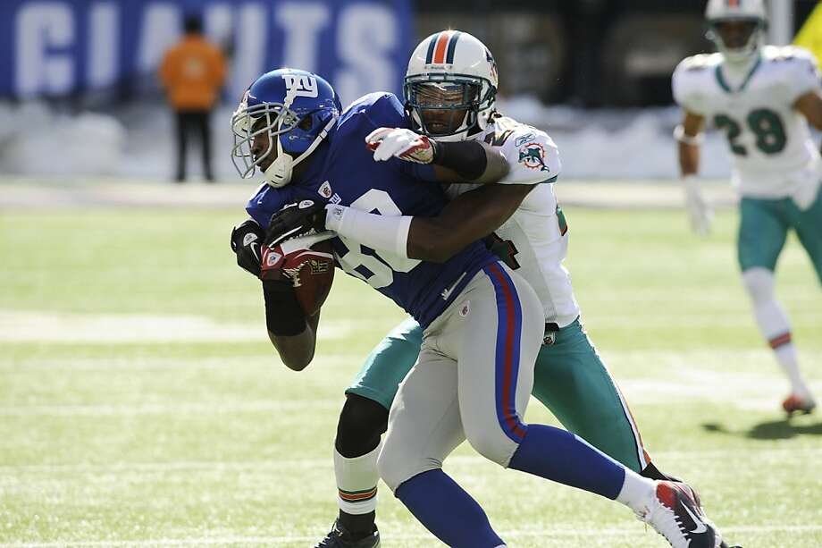 Miami Dolphins cornerback Sean Smith (24) tackles New York Giants wide receiver Hakeem Nicks (88) during the first quarter of an NFL football game Sunday, Oct. 30, 2011 in East Rutherford, N.J. (AP Photo/Bill Kostroun)  Ran on: 10-31-2011 Giants receiver Hakeem Nicks left with a hamstring injury late in the victory over the Dolphins. Ran on: 10-31-2011 Giants receiver Hakeem Nicks left with a hamstring injury late in the victory over the Dolphins. Photo: Bill Kostroun, AP
