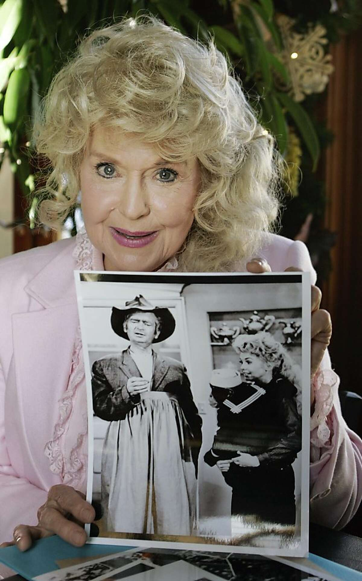 """FILE - In this Jan. 8, 2009 photo, Donna Douglas, who starred in the television series """"The Beverly Hillbillies"""" poses with a photo from the show in Baton Rouge, La. The actress who played Elly May Clampett on the show, toymaker Mattel Inc. and CBS Consumer Products Inc. have settled a lawsuit in which Douglas claimed the companies didn't get her approval to use her name and likeness for a Barbie doll. A one-sentence order Tuesday, Dec. 27, 2011 in U.S. District Court in Baton Rouge said only that a settlement had been reached. (AP Photo/Bill Haber)"""