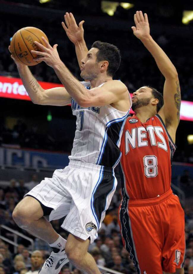 Orlando's J.J. Redick (left), who finished with 15 points, goes up for a shot in front of New Jersey's Deron Williams. Photo: AP