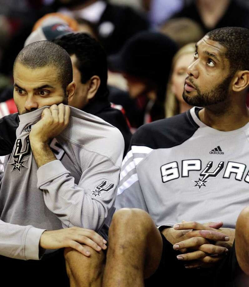 San Antonio Spurs guard Tony Parker, left, of France, and center Tim Duncan, right, sit on the bench during the fourth quarter of an NBA basketball game against the Houston Rockets, Thursday, Dec. 29, 2011, in Houston. The Rockets won 105-85. Photo: AP