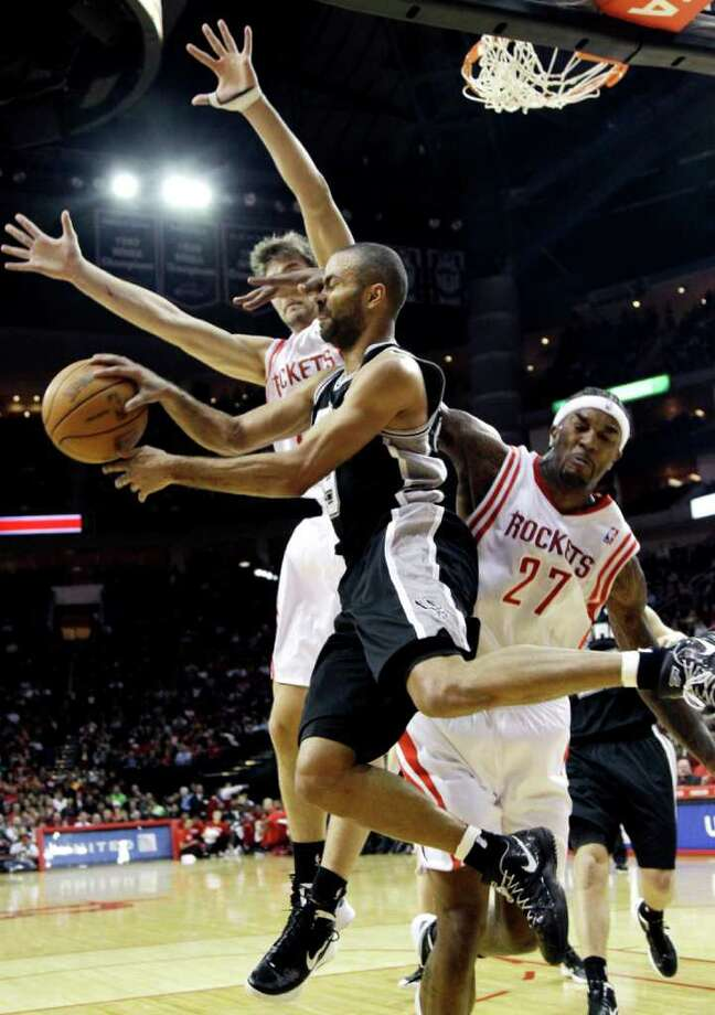 San Antonio Spurs' Tony Parker (9) is hit in the face by Houston Rockets' Jordan Hill (27) as he passes the ball during the first quarter of an NBA basketball game, Thursday, Dec. 29, 2011, in Houston. Photo: AP