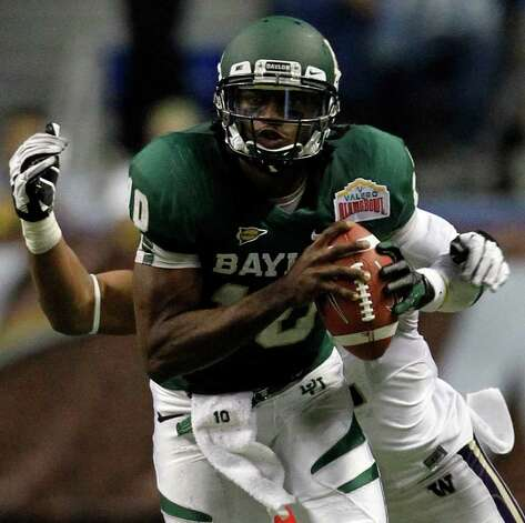 FOR SPORTS - Baylor's Robert Griffin III is tackled from behind by Washington's Josh Shirley during game action of the 2011 Valero Alamo Bowl at the Alamodome in San Antonio, Texas on Thursday, Dec. 29, 2011. MICHAEL MILLER / mmiller@express-news.net Photo: MICHAEL MILLER, SAN ANTONIO EXPRESS-NEWS / mmiller@express-news.net