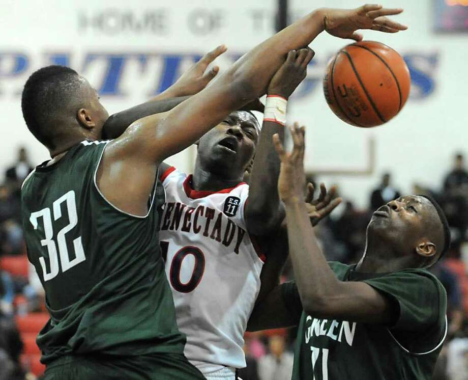 Jallah Tarver of Schenectady is stopped by Green Tech's Kristopher Clark, left, and Jafari Coleman as he drives to the hoop during the Hilliard Basketball Tournament at Schenectady High School Thursday, Dec. 29, 2011 in Schenectady, N.Y. (Lori Van Buren / Times Union) Photo: Lori Van Buren