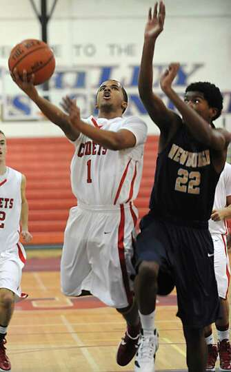 From left, Darrien White of Albany Academy drives to the basket against Elijah Ghrael of Newburgh Fr