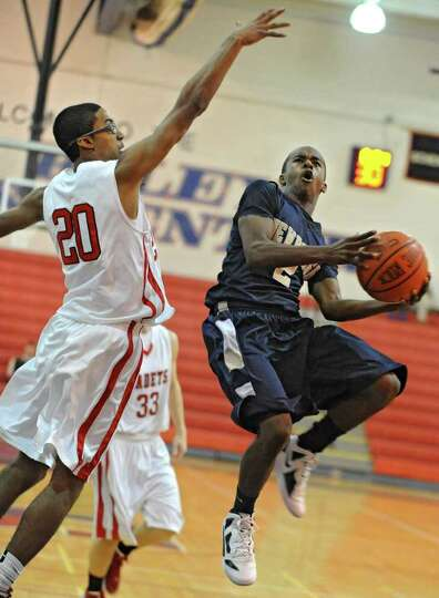 Donovan Fields of Newburgh Free Academy drives to the basket against Jelanie Curry of Albany Academy
