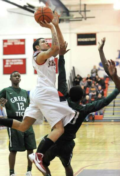 Cris Verestin of Schenectady drives to the basket against Tyler Victoria of Green Tech during the Hi