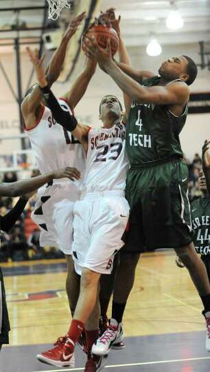 From left, Randall Symes and Danssel Rodriguez of Schenectady battle for a rebound with Lewis Jackso