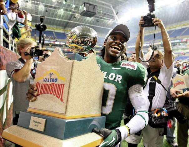 FOR SPORTS - Baylor's Robert Griffin III carries the trophy after the 2011 Valero Alamo Bowl with Washington Thursday Dec. 29, 2011 at the Alamodome in San Antonio,Tx. Baylor won 67-56. (PHOTO BY EDWARD A. ORNELAS/eaornelas@express-news.net) Photo: EDWARD A. ORNELAS, SAN ANTONIO EXPRESS-NEWS / SAN ANTONIO EXPRESS-NEWS (NFS)