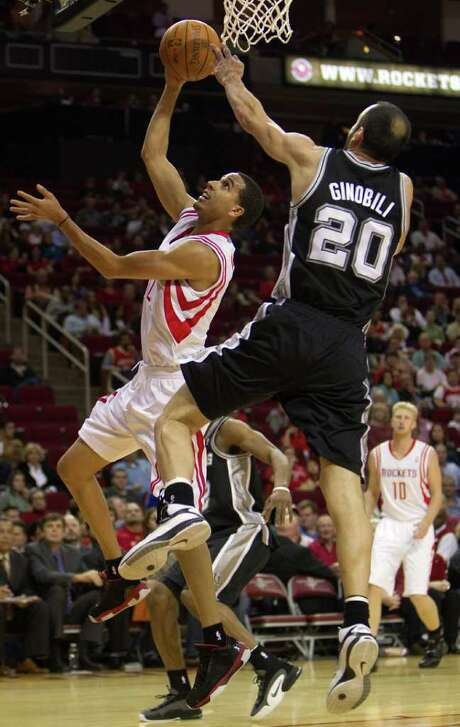 Smiley N. Pool: Chronicle PLAYING TWISTER: Rockets guard Kevin Martin (12) contorts himself to try to coax in a layup against the Spurs' Manu Ginobili (20). Martin wound up with a game-high 25 points. Photo: Smiley N. Pool / © 2011  Houston Chronicle