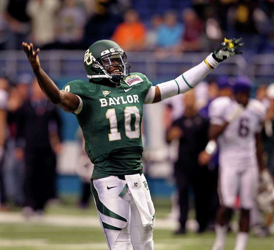 SPORTS  Robert Griffin III raise his arms in celebration as he runs away from players at the end of the game as Baylor beats Washington 67-56  in the Valero Alamo Bowl at the Alamodome in San Antonio, Texas  on December 29, 2011 Tom Reel/Staff Photo: TOM REEL, SAN ANTONIO EXPRESS-NEWS / © 2011 San Antonio Express-News
