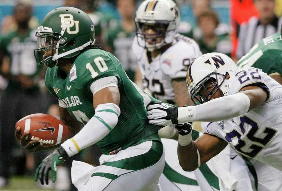 Baylor quarterback Robert Griffin III, left, is brought down by Washington's Josh Shirley during the first half of the Alamo Bowl college football game, Thursday, Dec. 29, 2011, at the Alamodome in San Antonio. (AP Photo/Darren Abate) Photo: Darren Abate / FR115 AP