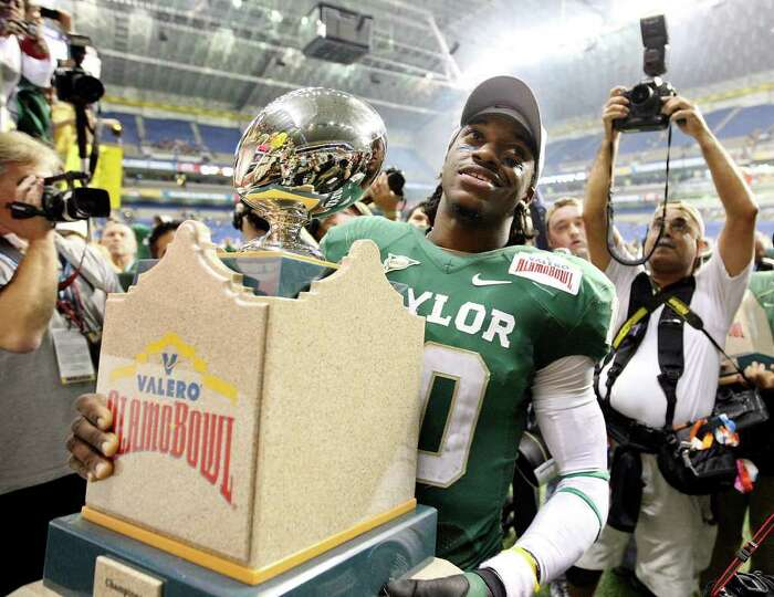 FOR SPORTS - Baylor's Robert Griffin III carries the trophy after the 2011 Valero Alamo Bowl with Wa