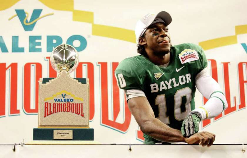 Baylor's Robert Griffin III stands with the trophy after the 2011 Valero Alamo Bowl with Washingt