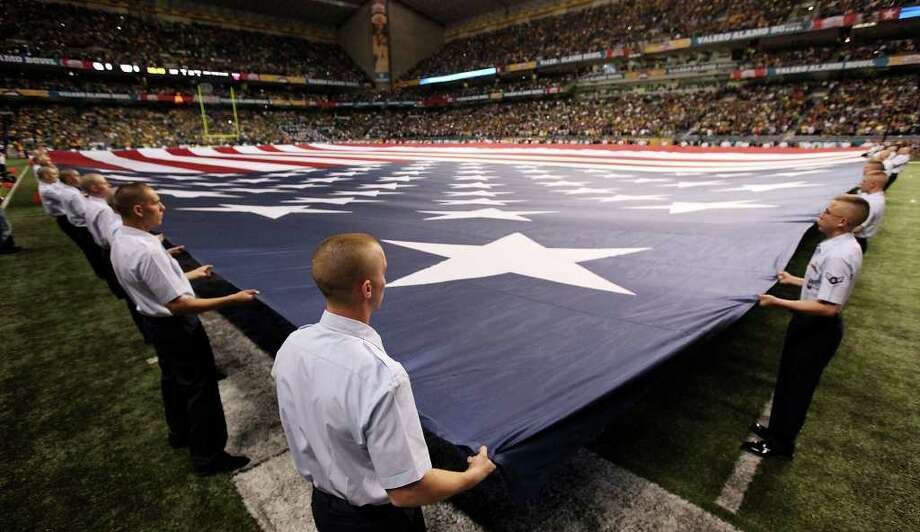 FOR SPORTS - U.S. Air Force trainees from Lackland AFB hold an American flag before the  2011 Valero Alamo Bowl with Baylor and Washington Thursday Dec. 29, 2011 at the Alamodome in San Antonio,Tx. Baylor won 67-56. (PHOTO BY EDWARD A. ORNELAS/eaornelas@express-news.net) Photo: EDWARD A. ORNELAS, SAN ANTONIO EXPRESS-NEWS / SAN ANTONIO EXPRESS-NEWS (NFS)