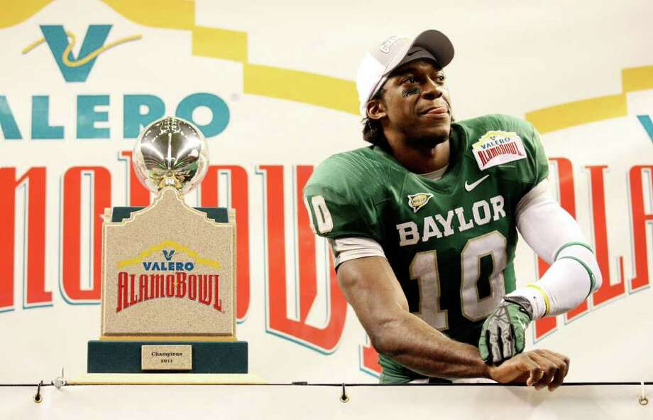 FOR SPORTS - Baylor's Robert Griffin III stands with the trophy after the 2011 Valero Alamo Bowl with Washington Thursday Dec. 29, 2011 at the Alamodome in San Antonio,Tx. Baylor won 67-56. (PHOTO BY EDWARD A. ORNELAS/eaornelas@express-news.net) Photo: EDWARD A. ORNELAS, SAN ANTONIO EXPRESS-NEWS / SAN ANTONIO EXPRESS-NEWS (NFS)