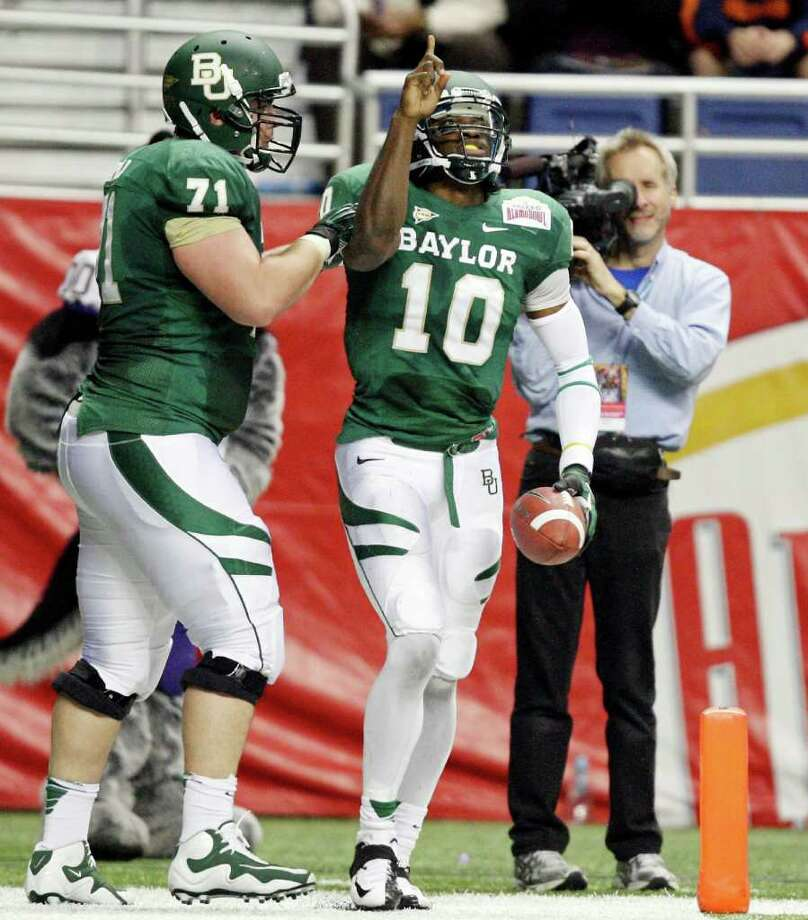 FOR SPORTS - Baylor's Robert Griffin III celebrates  with teammate Baylor's Cameron Kaufhold after scoring a touchdown against Washington during first half action of the 2011 Valero Alamo Bowl Thursday Dec. 29, 2011 at the Alamodome in San Antonio,Tx.  (PHOTO BY EDWARD A. ORNELAS/eaornelas@express-news.net) Photo: EDWARD A. ORNELAS, SAN ANTONIO EXPRESS-NEWS / SAN ANTONIO EXPRESS-NEWS (NFS)