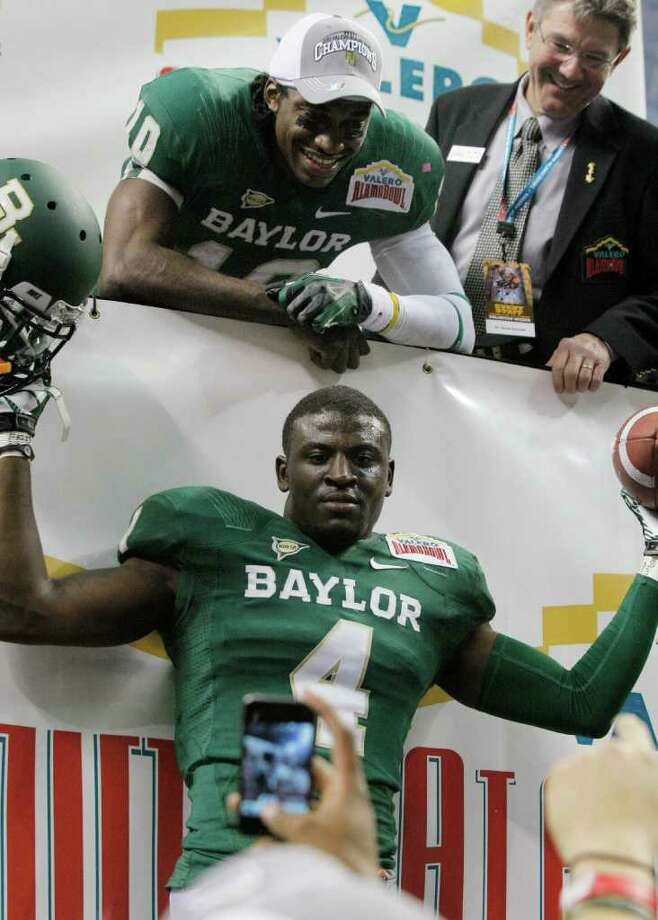 Baylor's Robert Griffin III, top, and Isaac Williams pose for a photograph after the Alamo Bowl college football game against Washington, Thursday, Dec. 29, 2011, at the Alamodome in San Antonio. Baylor pulled out a thrilling Alamo Bowl victory in the highest-scoring bowl game in history, beating Washington 67-56 in a record-smashing shootout Thursday night. (AP Photo/Darren Abate) Photo: Darren Abate, Associated Press / FR115 AP