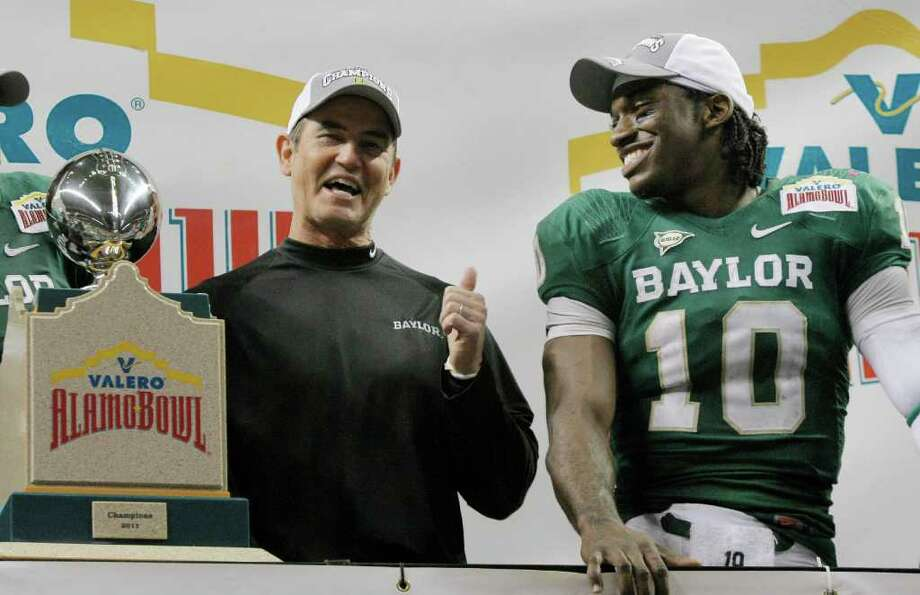 Baylor head coach Art Briles, left, and Baylor quarterback Robert Griffin III celebrate after the Alamo Bowl college football game, Thursday, Dec. 29, 2011, at the Alamodome in San Antonio. Baylor pulled out a thrilling Alamo Bowl victory in the highest-scoring bowl game in history, beating Washington 67-56 in a record-smashing shootout Thursday night. (AP Photo/Darren Abate) Photo: Darren Abate, Associated Press / FR115 AP