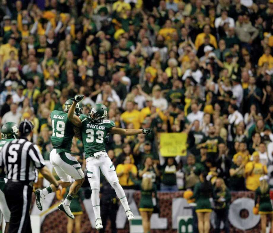 Baylor's LeQuince McCall, left, and Josh Wilson, celebrate a touchdown during the second half of the Alamo Bowl college football game against Washington, Thursday, Dec. 29, 2011, at the Alamodome in San Antonio. Baylor pulled out a thrilling Alamo Bowl victory in the highest-scoring bowl game in history, beating Washington 67-56 in a record-smashing shootout Thursday night. (AP Photo/Darren Abate) Photo: Darren Abate, Associated Press / FR115 AP