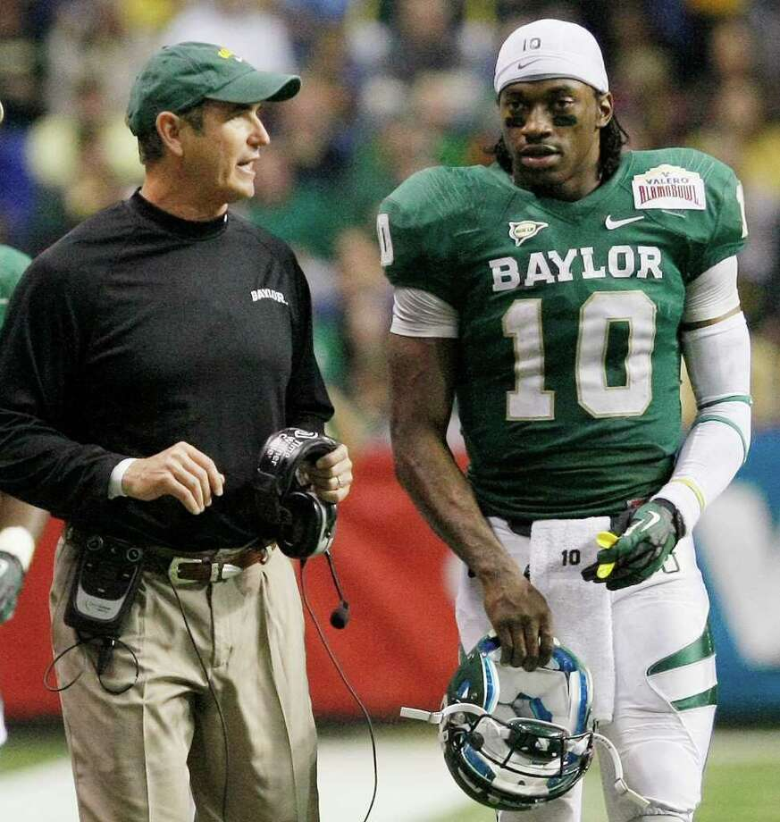 Baylor head coach Art Briles, left, and quarterback Robert Griffin III talk during the second half of the Alamo Bowl college football game against Washington, Thursday, Dec. 29, 2011, at the Alamodome in San Antonio. Baylor pulled out a thrilling Alamo Bowl victory in the highest-scoring bowl game in history, beating Washington 67-56 in a record-smashing shootout Thursday night. (AP Photo/Darren Abate) Photo: Darren Abate, Associated Press / FR115 AP