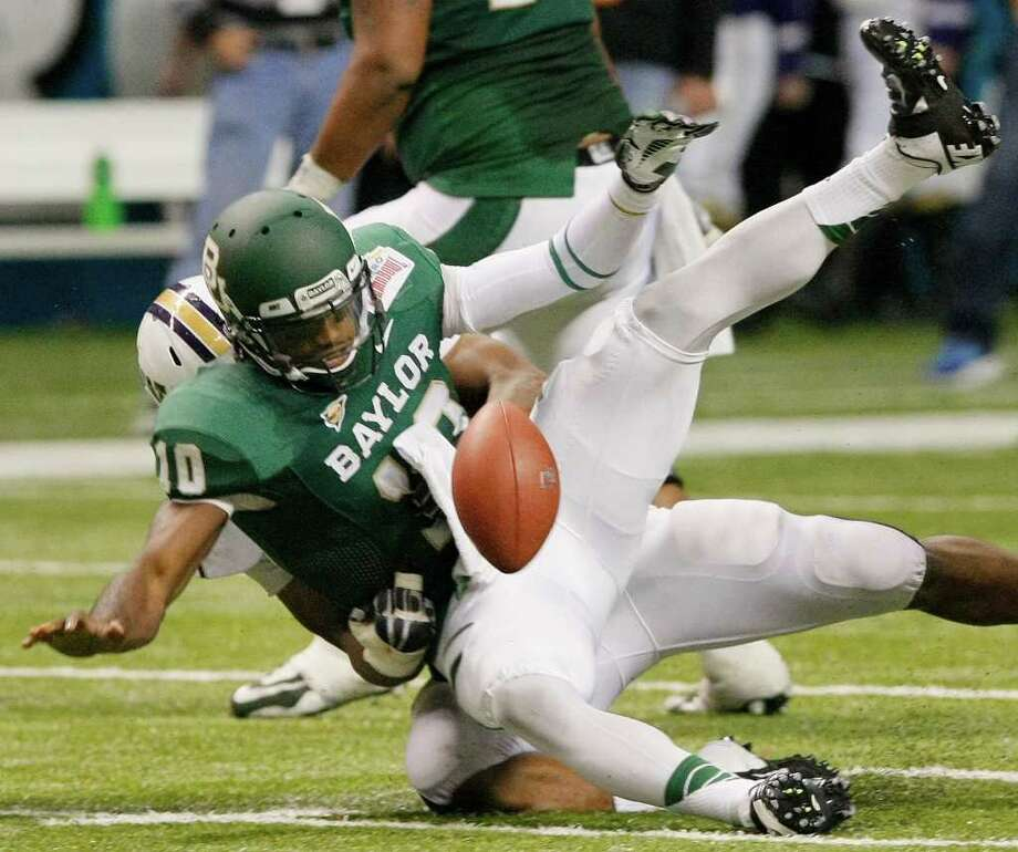 Baylor quarterback Robert Griffin III fumbles the ball as he is sacked by Washington's Andrew Hudson, rear, during the first half of the Alamo Bowl college football game, Thursday, Dec. 29, 2011, at the Alamodome in San Antonio. Washington recovered the ball. (AP Photo/Darren Abate) Photo: Darren Abate, Associated Press / FR115 AP