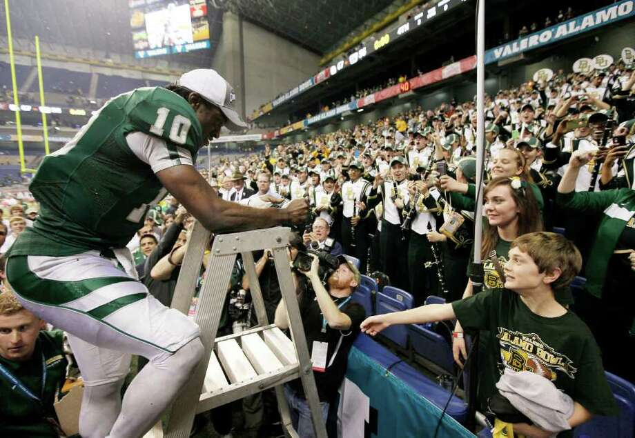 Baylor's Robert Griffin III celebrates with fans after the Alamo Bowl college football game against Washington, Thursday, Dec. 29, 2011, at the Alamodome in San Antonio. Baylor pulled out a thrilling Alamo Bowl victory in the highest-scoring bowl game in history, beating Washington 67-56 in a record-smashing shootout Thursday night. (AP Photo/Darren Abate) Photo: Darren Abate, Associated Press / FR115 AP