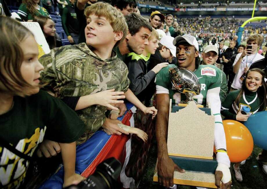 Baylor's Robert Griffin III, right, celebrates with fans after the Alamo Bowl college football game against Washington, Thursday, Dec. 29, 2011, at the Alamodome in San Antonio. Baylor pulled out a thrilling Alamo Bowl victory in the highest-scoring bowl game in history, beating Washington 67-56 in a record-smashing shootout Thursday night. (AP Photo/Darren Abate) Photo: Darren Abate, Associated Press / FR115 AP