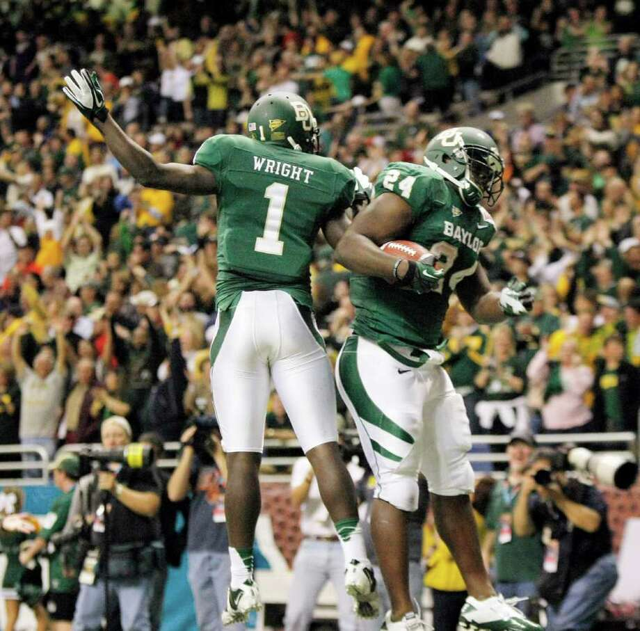 Baylor's Terrance Ganaway, right, and Kendall Wright celebrate a touchdown during the second half of the Alamo Bowl college football game against Washington, Thursday, Dec. 29, 2011, at the Alamodome in San Antonio. Baylor pulled out a thrilling Alamo Bowl victory in the highest-scoring bowl game in history, beating Washington 67-56 in a record-smashing shootout Thursday night. (AP Photo/Darren Abate) Photo: Darren Abate, Associated Press / FR115 AP