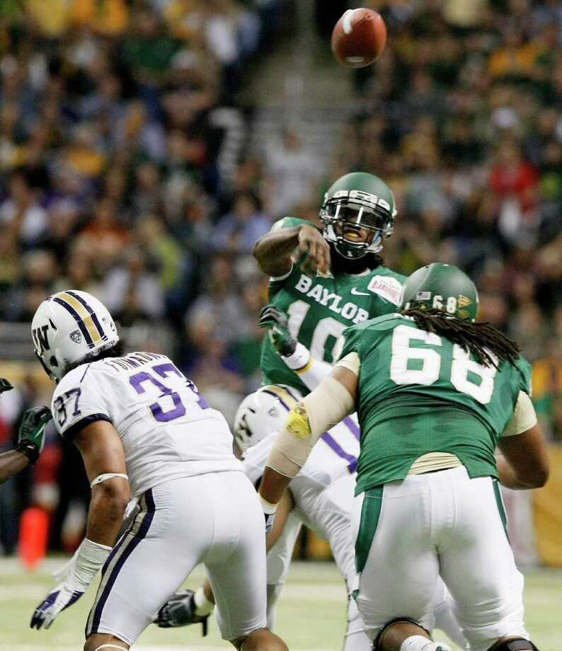 Baylor quarterback Robert Griffin III, rear, throws a pass during the first half of the Alamo Bowl college football game against Washington, Thursday, Dec. 29, 2011, at the Alamodome in San Antonio. (AP Photo/Darren Abate) Photo: Darren Abate, Associated Press / FR115 AP