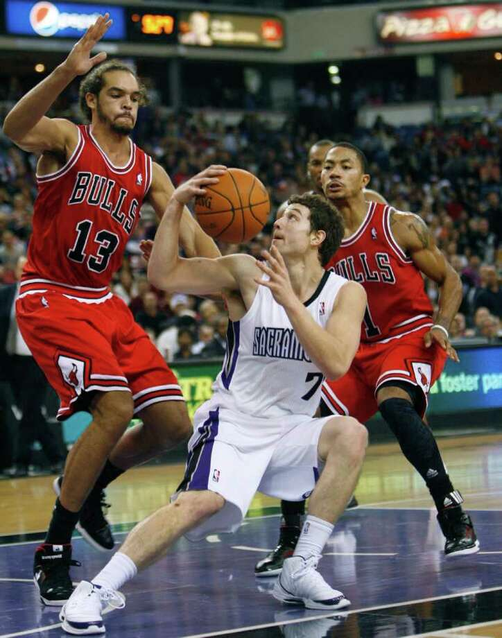 Sacramento Kings guard Jimmer Fredette (7) drives against Chicago Bulls defenders Joakim Noah (13) and Derrick Rose during the second half of an NBA basketball game in Sacramento, Calif., on Thursday, Dec. 29, 2011. The Bulls won 108-98. (AP Photo/Steve Yeater) Photo: Steve Yeater