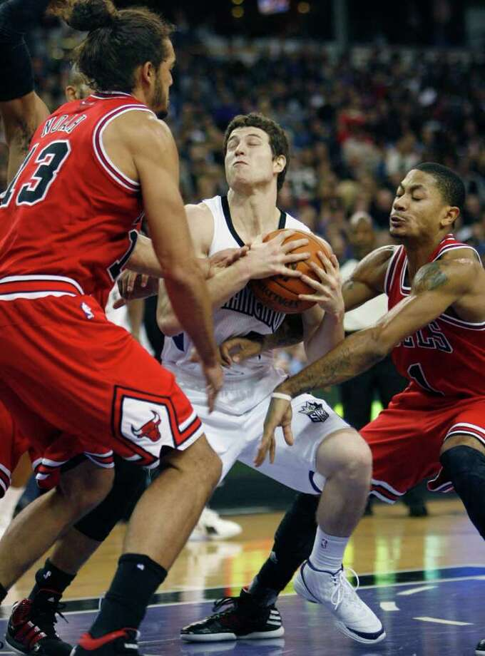 Sacramento Kings guard Jimmer Fredette, center, is trapped by Chicago Bulls defenders Joakim Noah, left, and Derrick Rose during the second half of an NBA basketball game in Sacramento, Calif., on Thursday, Dec. 29, 2011. The Bulls won 108-98. (AP Photo/Steve Yeater) Photo: Steve Yeater