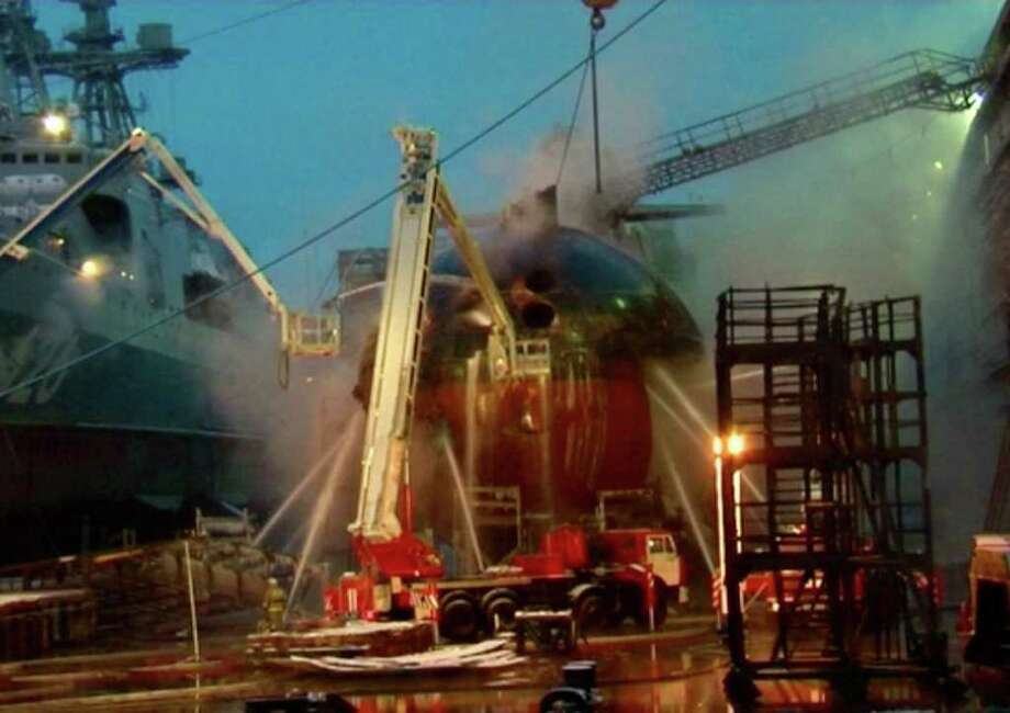 In this video image from Ru-RTR Russian state television channel, firefighters spray water on the Yekaterinburg nuclear submarine in a dock at the Roslyakovo shipyard in the Murmansk region, Russia, Friday, Dec. 30, 2011. A fire that erupted while the Yekaterinburg was in drydock for repairs at the town of Roslyakovo near Murmansk has left seven crewmembers injured after they inhaled poisonous fumes from the blaze. (AP Photo/Ru-RTR Russian state channel/ Via APTN) / RU-RTR Russian State Channel via