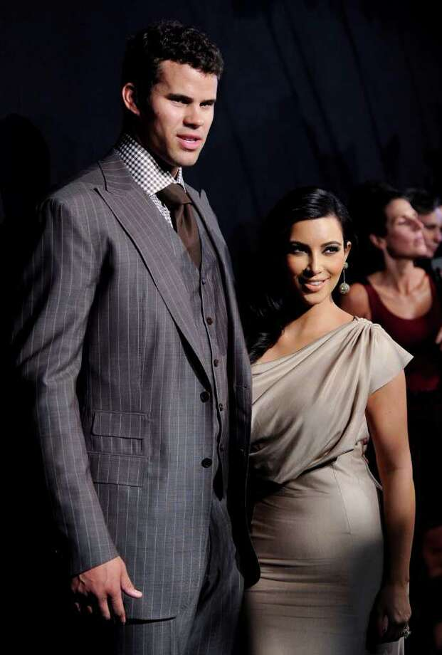 FILE - In this Aug. 31, 2011 file photo, newlyweds Kim Kardashian, right, and Kris Humphries attend a party thrown in their honor in New York. Kardashian is expected to file for divorce in Los Angeles on Monday, Oct. 31, 2011, according to a report confirmed by the producers of her reality show. Kardashian and Humphries were married on Aug. 20. (AP Photo/Evan Agostini, file) Photo: Evan Agostini / AP2011