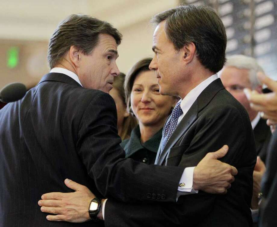Texas Gov. Rick Perry (left) embraces Speaker of the House Joe Straus as the 82nd Texas Legislature opens. Nothing was done during the session to fix the so-called margins  tax. Photo: Associated Press, Eric Gay / AP