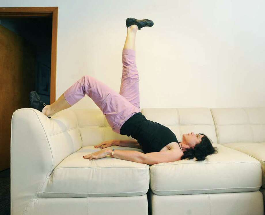 KEVIN MINGORA PHOTOS :  ALLENTOWN MORNING CALL BRIDGE KICK: Author Selene Yeager demonstrates the finishing position of the bridge kick couch exercise, which helps to tone the butt and thighs. Photo: Kevin Mingora / Allentown Morning Call