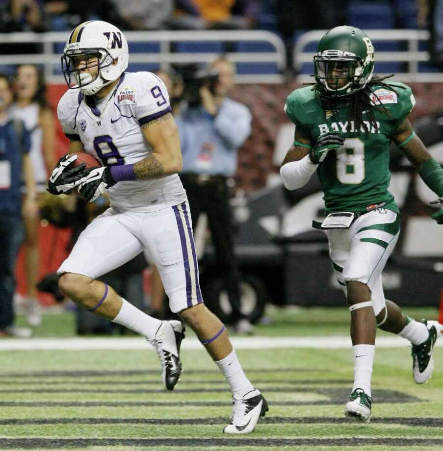 Washington's Devin Aguilar, left, makes a touchdown reception ahead of Baylor's K.J. Morton during the second half of the Alamo Bowl college football game, Thursday, Dec. 29, 2011, at the Alamodome in San Antonio. Baylor pulled out a thrilling Alamo Bowl victory in the highest-scoring bowl game in history, beating Washington 67-56 in a record-smashing shootout Thursday night. Photo: AP