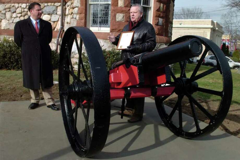 Milford Mayor Ben Blake, left, listens as Peter Spaltoff speaks at the unveiling of the Fort Trumbull cannon in its new location in front of the Milford Chamber of Commerce, in Milford, Conn. Dec. 30th, 2011. Spaltoff lead the restoration of the cannon, much of which was done by students at Platt Tech. Photo: Ned Gerard / Connecticut Post